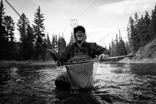 Man catching fish with net and rod on a river in black and white