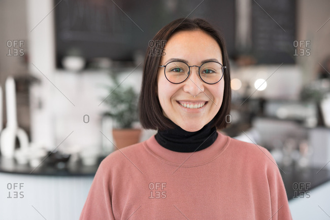 Portrait of an Asian woman with glasses in a coffee shop