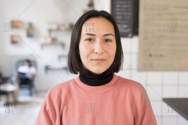 Portrait of an Asian woman standing in a coffee shop