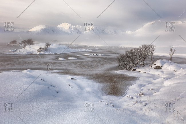 A snow covered Rannoch Moor looking over a frozen Lochan na h-achlaise to the misty Blackmount mountain range, Glencoe, Scotland