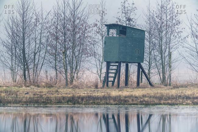 Deer hunting post in winter at edge of lake