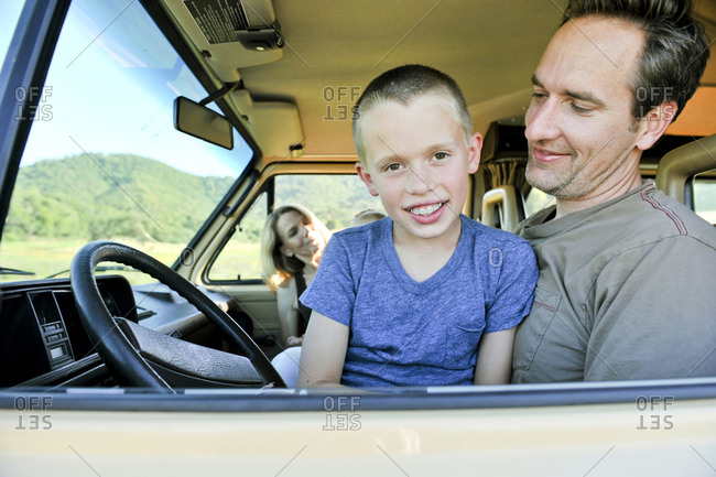 Portrait of son sitting on father with mother and brother in camper trailer