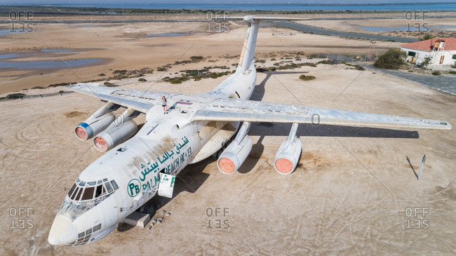 Umm Al Quwain, UAE - March 31, 2017: Aerial view of a girl waving on the top of the old abandoned russian cargo plane in Umm Al Quwain Airport