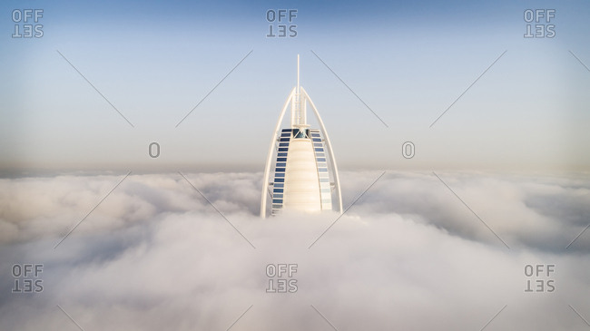 Dubai, UAE - April 23, 2017: Aerial view of the luxurious Burj Al Arab hotel crossing the clouds