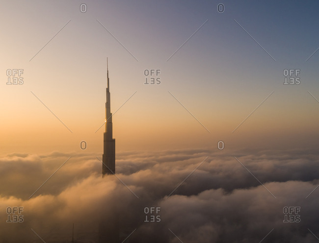 Dubai, UAE - June 21, 2017: Aerial view of Burj Khalifa tower in a sea of clouds at sunset