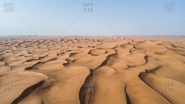 Aerial view of people driving quad bikes in the sand dunes of Al Bedayer desert in Sharjah, UAE