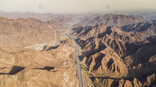 Aerial view of a road in the middle of rocky mountains in north Ras Al Khaimah, UAE