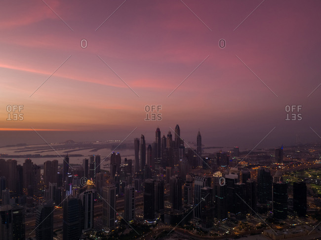 Aerial view of the Palm Jumeirah in background of the illuminated towers of Dubai at sunset, UAE
