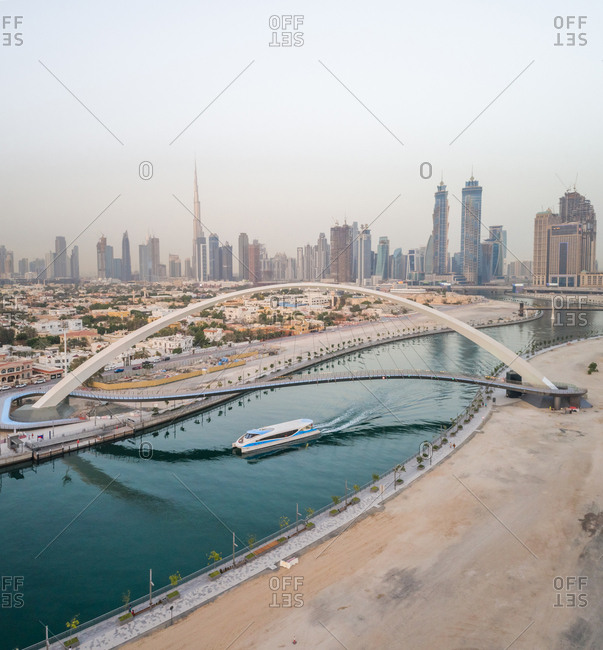 Aerial view of a yacht under the Tolerance pedestrian Bridge with Dubai skyscrapers in background, UAE
