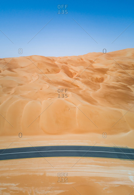 Aerial view of an empty curved road in the desert of Abu Dhabi, UAE