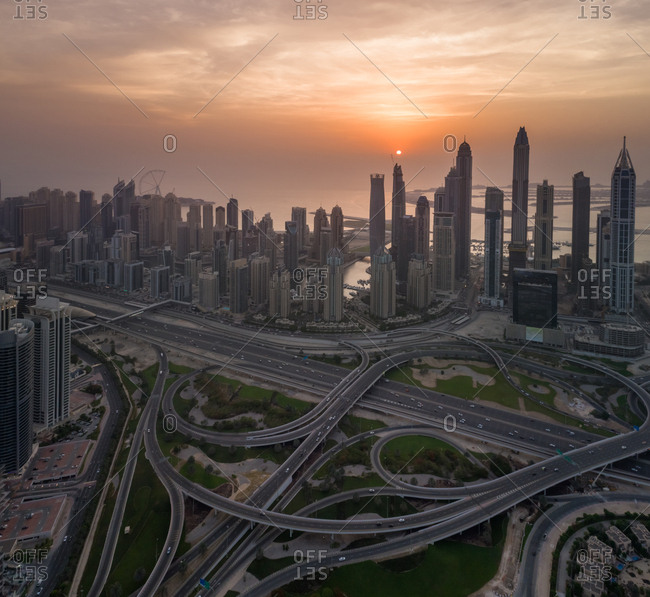 Aerial view of Dubai Marina with skyscrapers, traffic lines and the Palm Jumeirah in the background at sunset, UAE