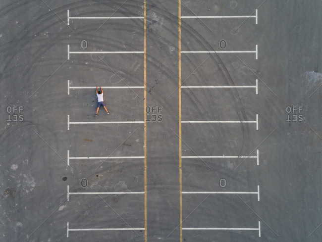 Aerial conceptual view of a man falling from a parking line in Dubai, UAE