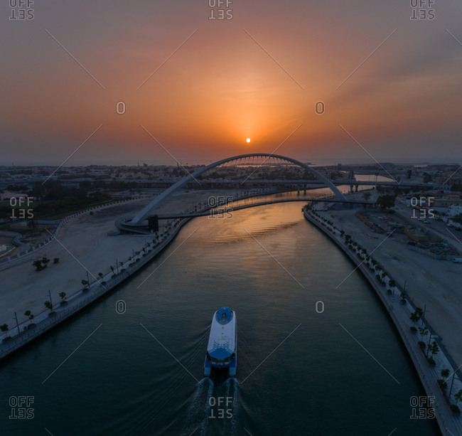 Aerial view of a boat under the Tolerance pedestrian Bridge in Dubai at sunset, UAE