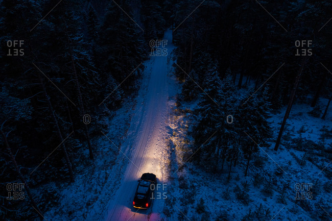 Aerial view of a car driving by night on the snowy road in the forest of Metsajarve in Estonia