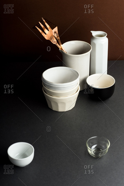 Various ceramic bowls and objects in dark brown setting with copper kitchen utensil