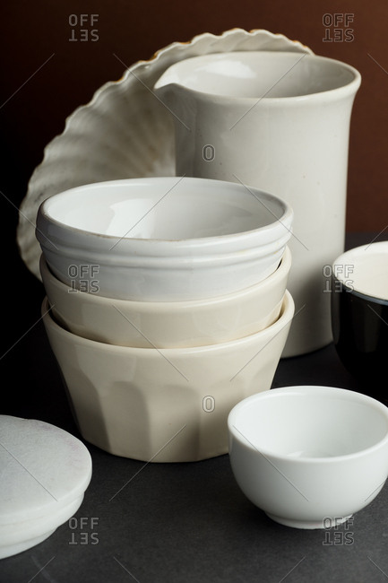 Close up of various ceramic bowls and kitchen objects in dark brown setting