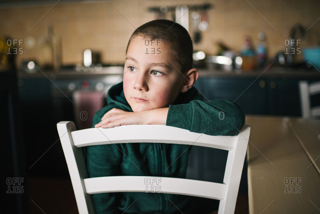 Boy resting head on kitchen chair, daydreaming