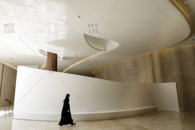 Dubai, United Arab Emirates - February 13, 2018: A woman walks by an architectural feature in the Etihad Museum