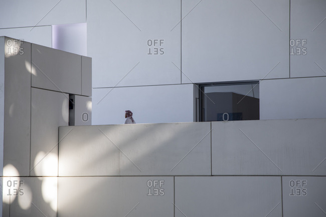 Abu Dhabi, United Arab Emirates - February 10, 2018: Visitor breaking up the hard angles of the Louvre in Abu Dhabi