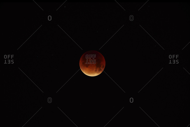 Long exposure showing a  red tinged moon with the majority in shadow during a full  lunar eclipse
