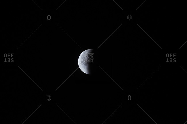 Almost half of the moon re-emerging from shadow after total lunar eclipse
