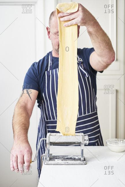 Chef feeding raw dough into pasta maker