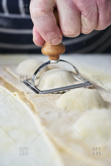 Close up of chef using stamp to cut out ravioli from raw pasta dough