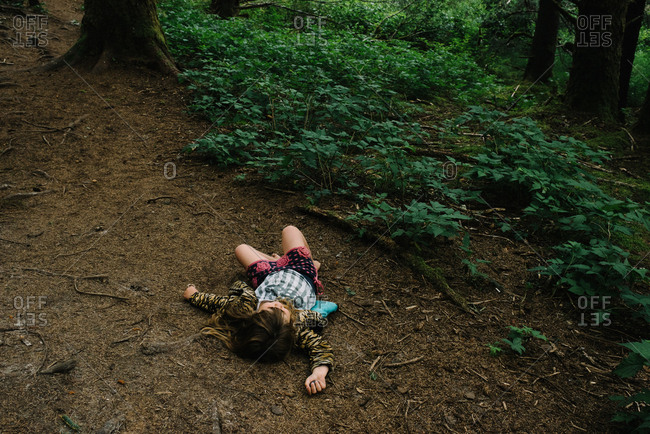 Little girl lying down in clearing in forest