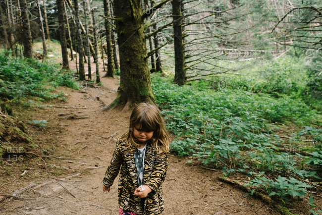 Unhappy little girl stomping along trail in woods