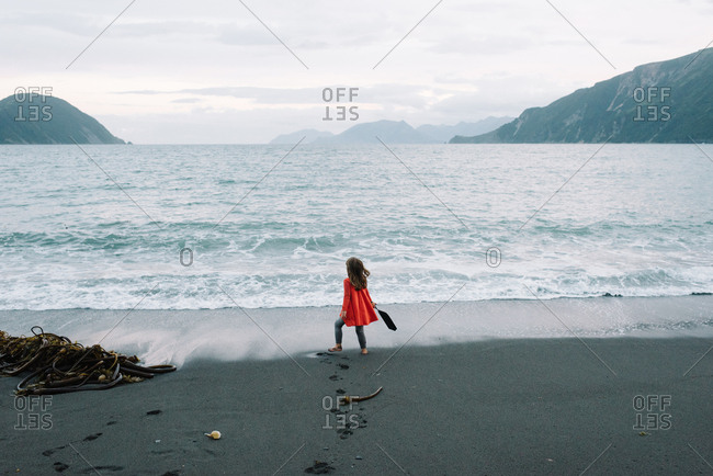 Rearview of little girl playing on remote beach in Alaska