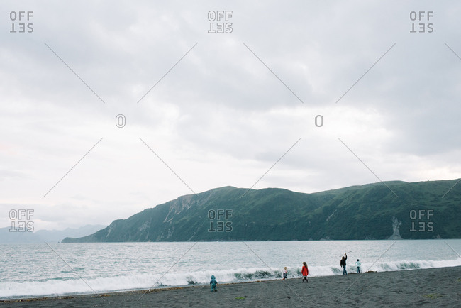 Kids exploring wild remote beach on a cloudy summers day in Alaska