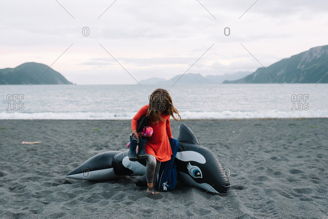 Little girl sitting on inflatable toy killer whale on wild remote beach in Alaska