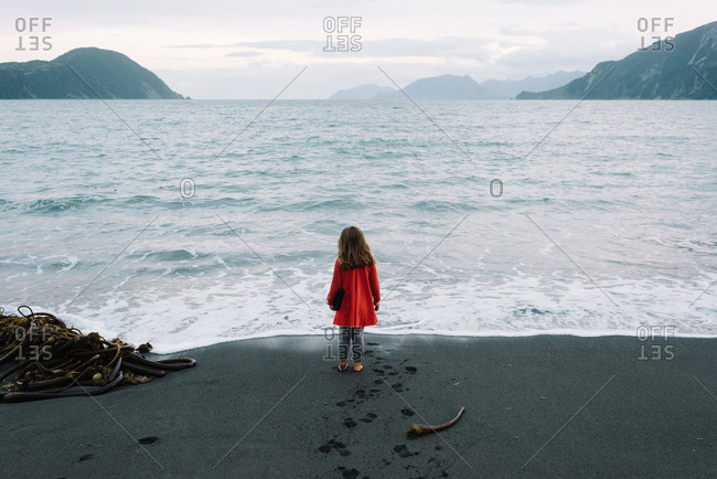 Rearview of little girl looking out to sea on remote beach in Alaska