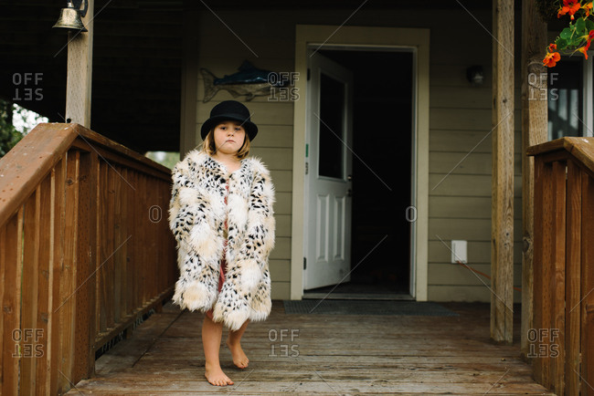 Little girl playing dress up on front porch of house