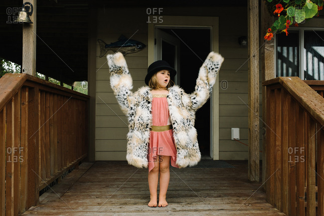 Little girl raising arms and calling out playing dress up on porch of house