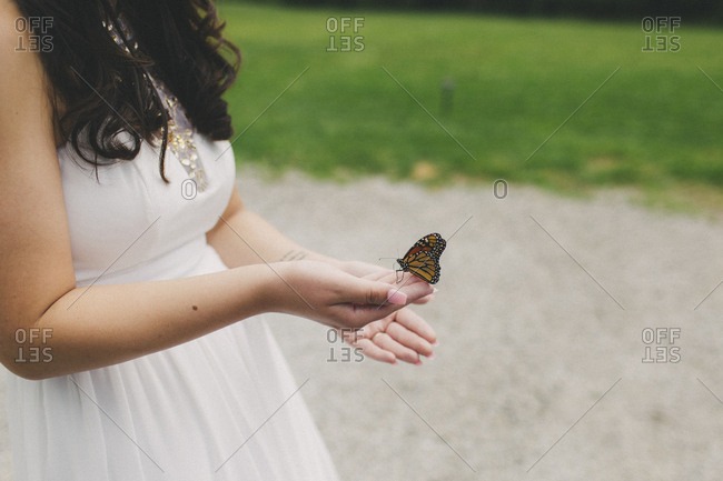 Bridesmaid holding monarch butterfly at outdoor wedding
