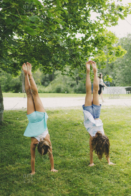 Two girls doing handstands at backyard wedding
