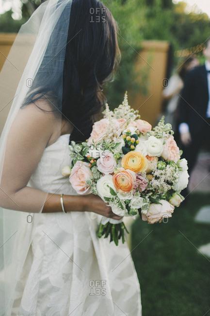 Bouquet detail of bride walking down aisle outside