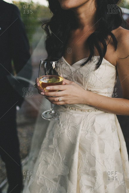 Newlywed bride enjoying glass of wine after wedding