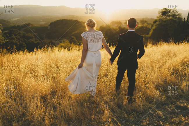 Newlywed portrait of couple walking towards sunset in golden field