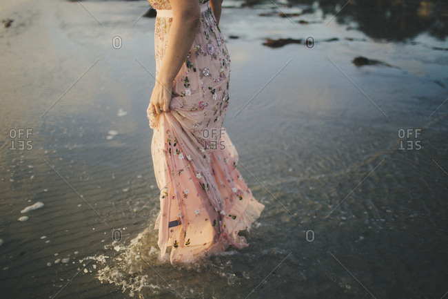 Woman walking through shallow water at beach engagement session