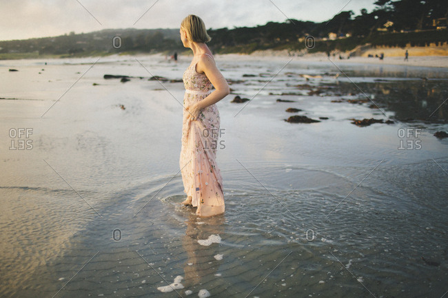 Coastal engagement portrait of female fiance in long gown gazing at sunset