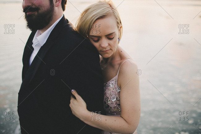 Future bride leaning on fiance at ocean engagement session