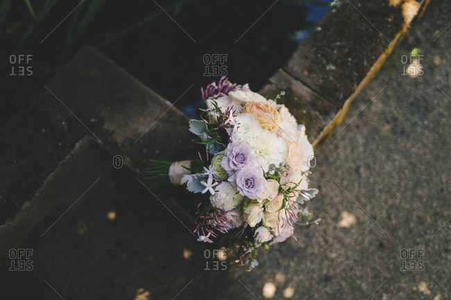 Top view of wedding bouquet resting on corner of concrete wall