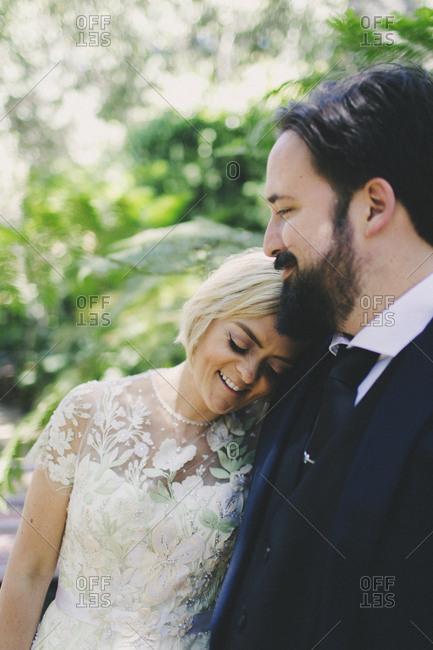 Happy newlyweds posing outside after wedding