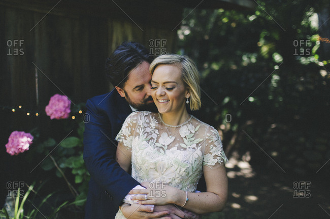 Groom hugging happy bride in outdoor wedding portrait