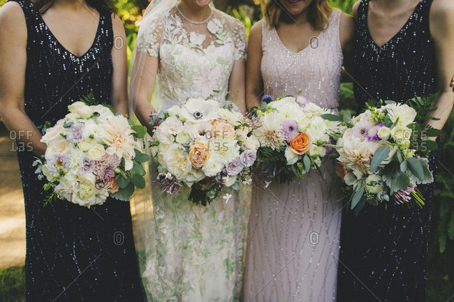 Bridal party portrait holding matching bouquets outside