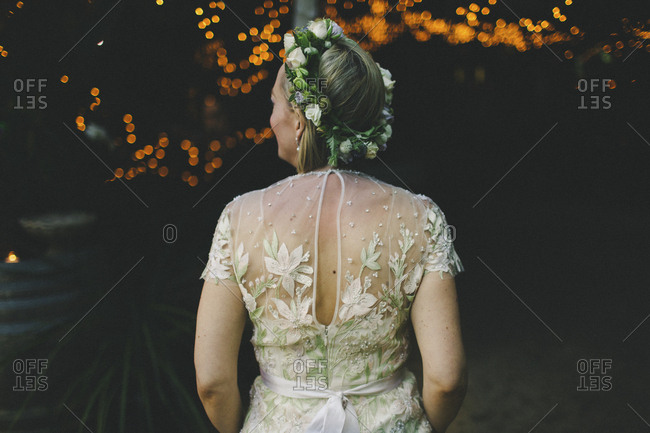 Back of bride with flower crown at night reception