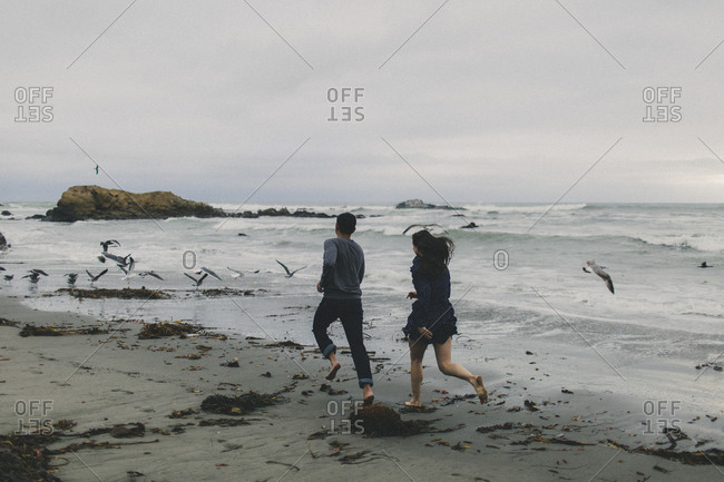 Young couple running barefoot on beach together  on a cloudy day