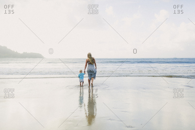 Mom and toddler walking through shallow water on shore towards ocean on a pretty day